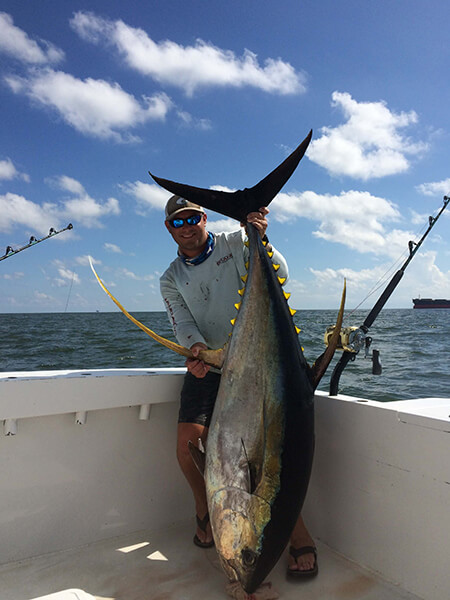 Man holding up large yellow fin tuna on boat in ocean