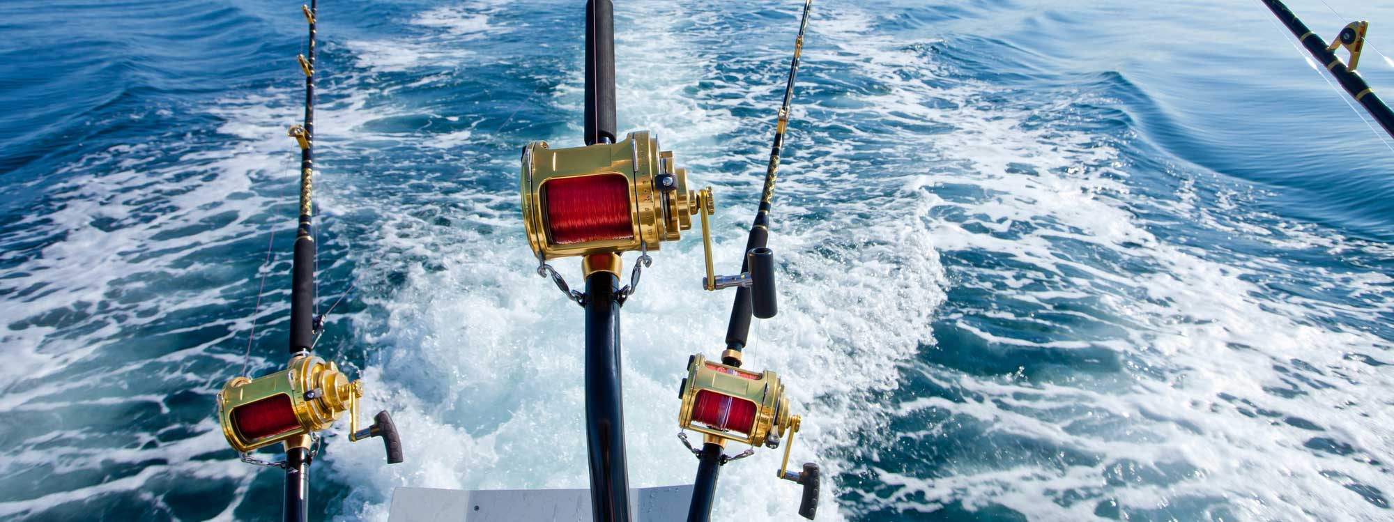 Three fishing reels off the back of a boat in the ocean